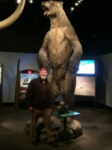 Author Charlie Sheldon beside a replica of a Short Face Bear, Royal Museum, Victoria, B.C. Photo by Randa Williams.